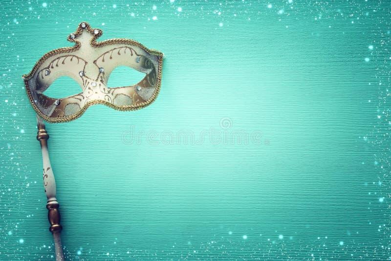 conceito da celebração do partido do carnaval com máscara elegante do ouro na vara sobre o fundo de madeira da hortelã Vista supe ilustração stock