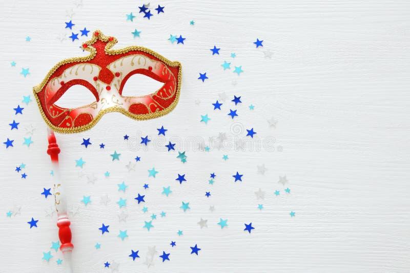 conceito da celebração do partido do carnaval com máscara vermelha elegante na vara sobre o fundo e as estrelas de madeira branco ilustração royalty free