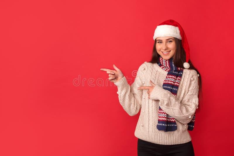 Conceito da celebração Jovem mulher na posição do lenço e do chapéu de Santa isolada no vermelho que aponta de lado o sorriso ale imagens de stock royalty free