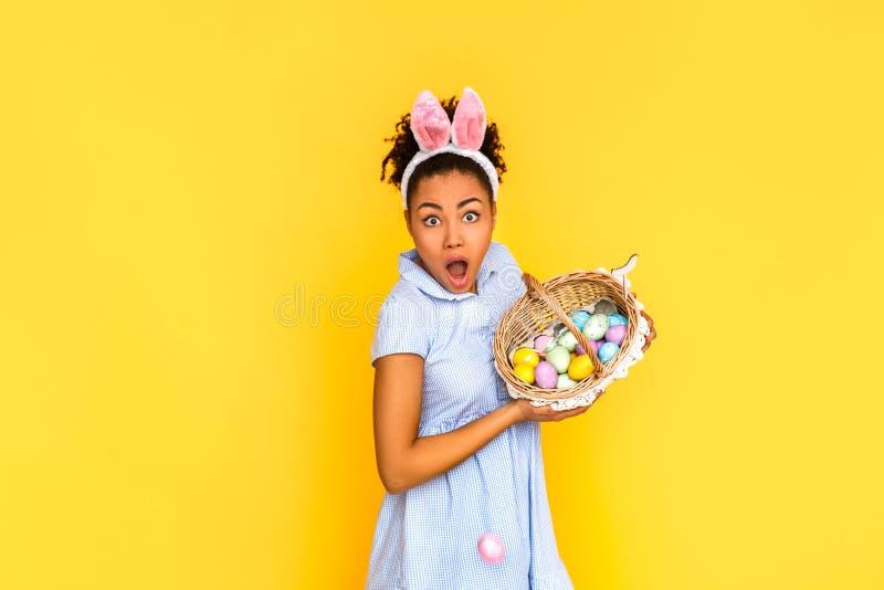 Conceito da celebra??o da P?scoa Jovem mulher na posição bonito das orelhas do vestido e do coelho isolada no amarelo com a cesta foto de stock royalty free
