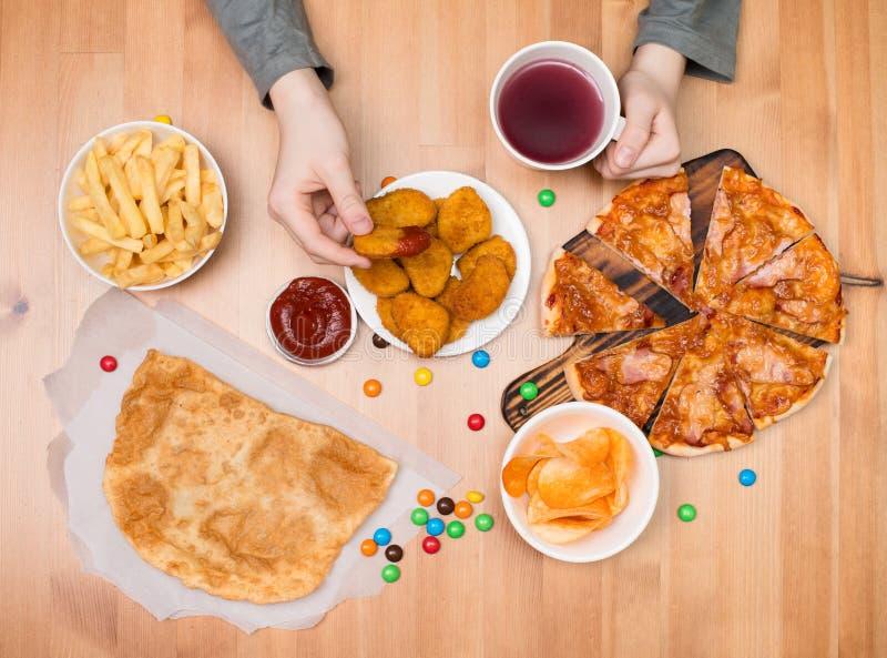 Conceito da comida lixo do fast food Caçoe comer pepitas, pizza, microplaquetas fotografia de stock