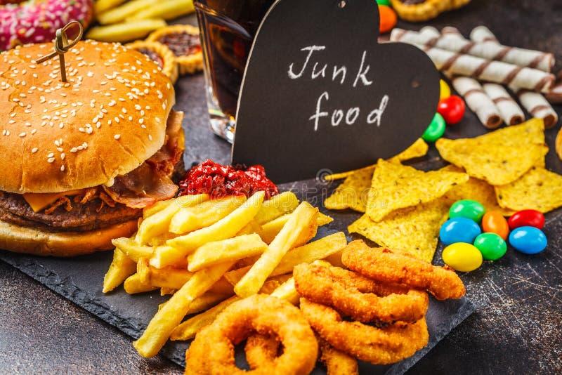 Conceito da comida lixo Fundo insalubre do alimento Fast food e açúcar Hamburguer, doces, microplaquetas, chocolate, anéis de esp imagens de stock royalty free
