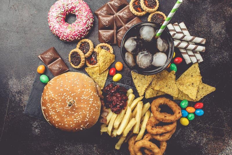 Conceito da comida lixo Fundo insalubre do alimento Fast food e açúcar Hamburguer, doces, microplaquetas, chocolate, anéis de esp foto de stock