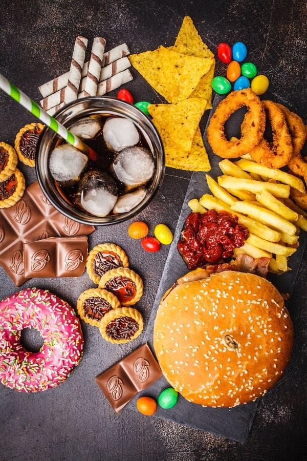 Conceito da comida lixo Fundo insalubre do alimento Fast food e açúcar Hamburguer, doces, microplaquetas, chocolate, anéis de esp fotos de stock