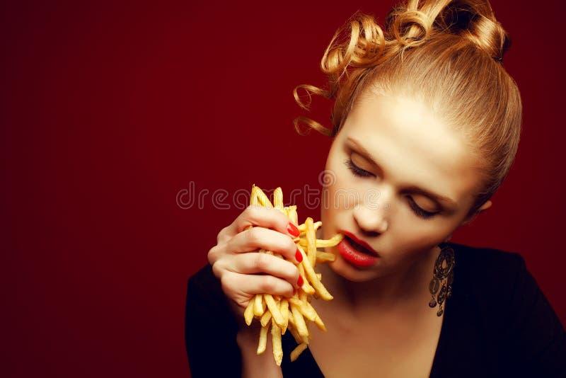 Conceito da comida lixo Menina que come fritadas fotos de stock