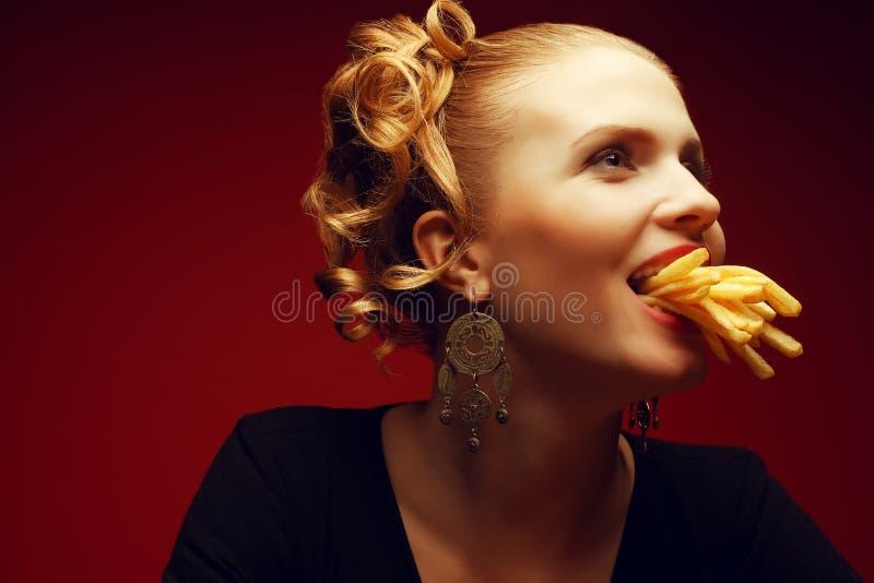 Conceito da comida lixo Menina que come fritadas foto de stock royalty free