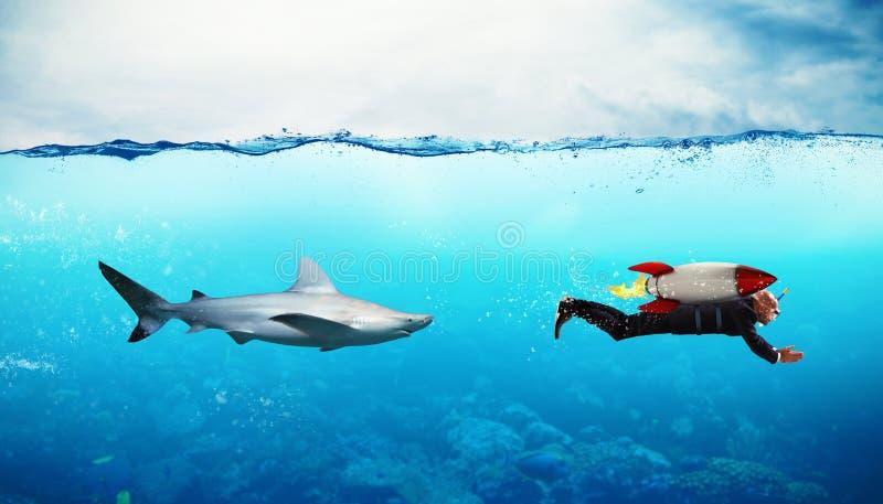Conceito da competição O homem de negócios escapa dos tubarões com um foguete fotografia de stock royalty free