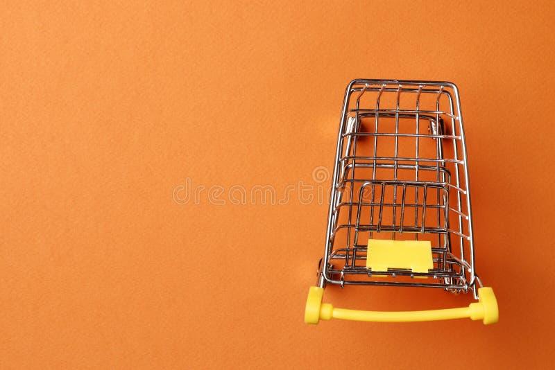 Conceito da compra carrinho de compras em um fundo amarelo fotografia de stock
