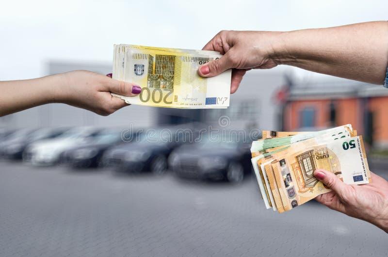 Conceito da compra do carro, m?os f?meas com euro- notas foto de stock