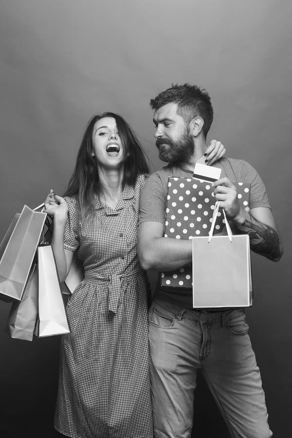 Conceito da compra e da forma O indivíduo com barba e a senhora bonita com cara feliz fazem a compra O homem farpado guarda cartõ imagens de stock