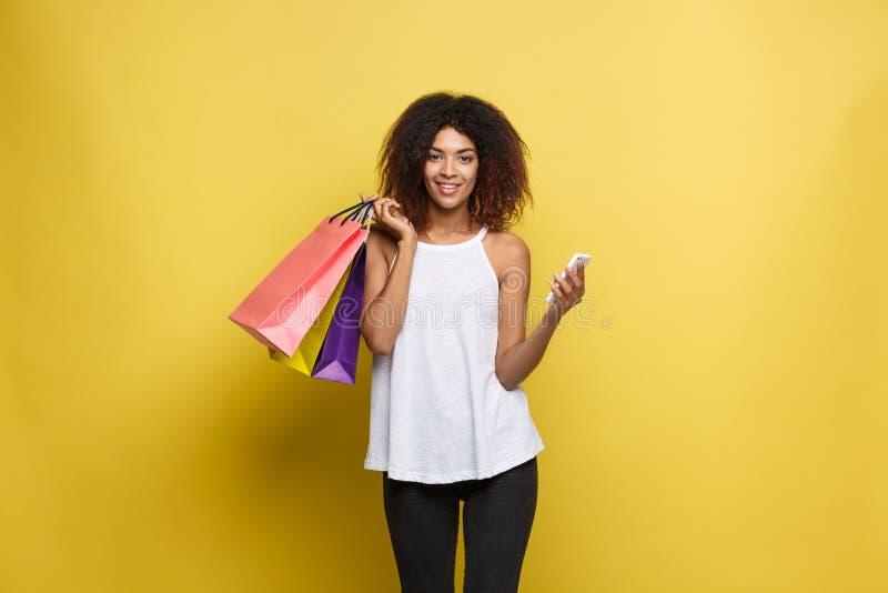 Conceito da compra - mulher africana atrativa bonita nova do retrato ascendente próximo que sorri e alegre com compra colorida imagens de stock royalty free