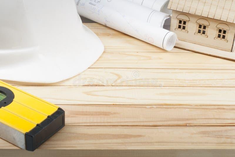Conceito da construção e do negócio Capacete branco, desenho, casa modelo e nível na tabela de madeira Copie o espaço para o text imagens de stock royalty free