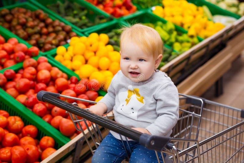 Conceito da consumição Bebê no carro que faz compras na mercearia no supermercado foto de stock royalty free