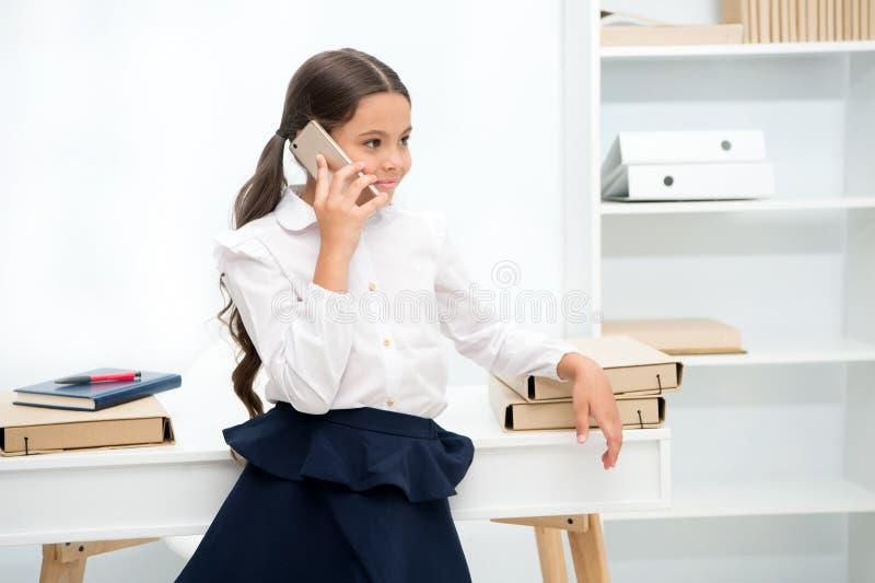 Conceito da conversa Conversa feliz da menina no telefone celular Smartphone do uso da criança pequena na escola Conversa no tele imagem de stock royalty free