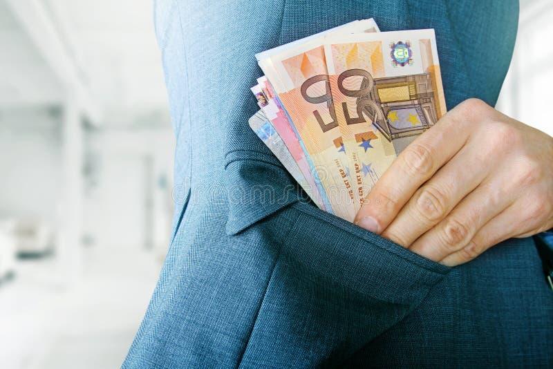 Conceito da corrupção, mão que põe o dinheiro no bolso do revestimento imagem de stock