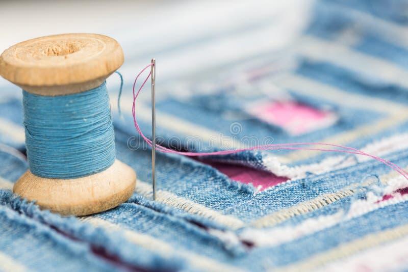 Conceito da costura e do bordado - a instalação do carretel de linhas azuis e decorado com uma matéria têxtil azul com teste padr imagem de stock