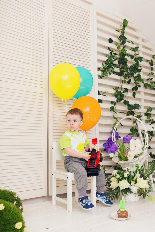 Conceito da criança, da festa de anos e da infância - rapaz pequeno com balões e brinquedos dentro imagem de stock royalty free