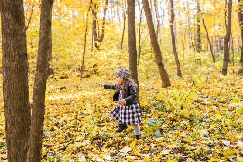 Conceito da criança, da natureza e de família - menina feliz que ri e que joga no outono na caminhada da natureza fora foto de stock royalty free