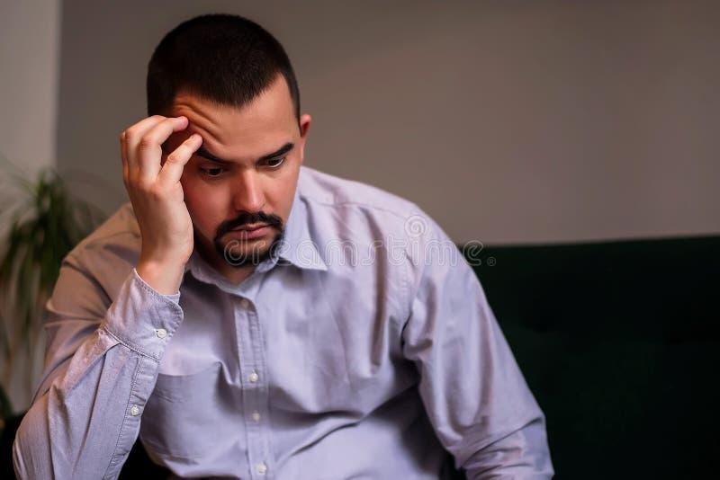 Conceito da crise do Midlife: retrato do assento de meia idade pensativo do homem interno com a sobrancelha aumentada que p?e a c foto de stock