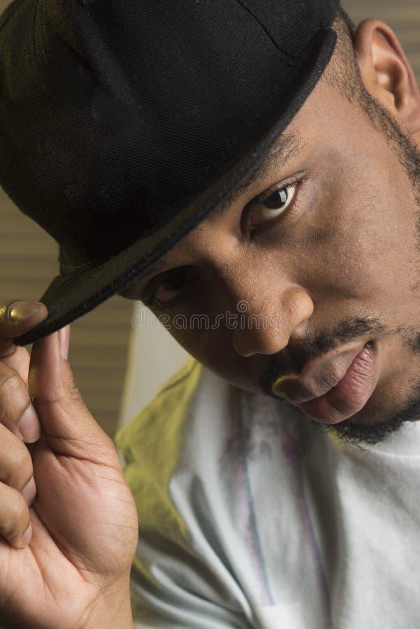 Conceito da cultura do rapper O preto macho com barba veste o tampão do rapper e olha considerável Homem na cara calma com grande imagens de stock