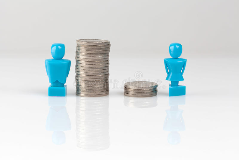 Conceito da desigualdade da renda com estatuetas e moedas foto de stock
