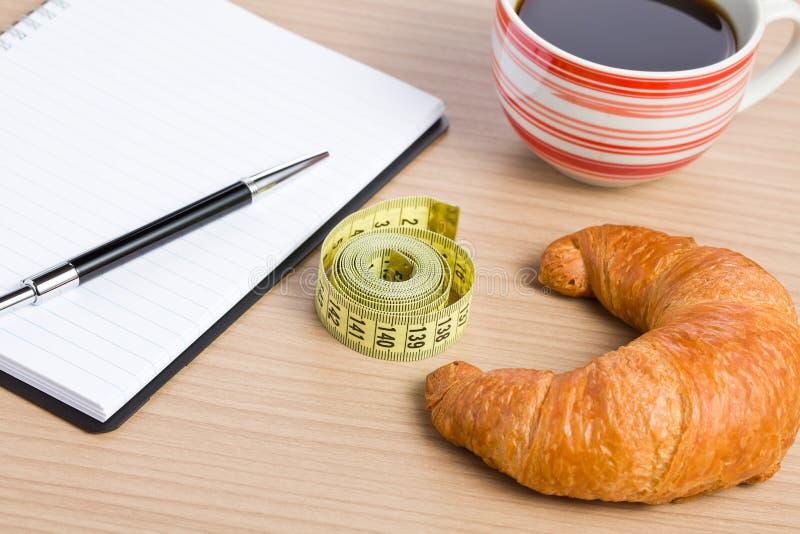 Conceito da dieta. croissant e fita de medição fotografia de stock