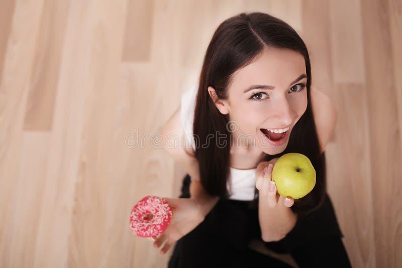 Conceito da dieta e do fast food Mulher excesso de peso que está em Weighin fotos de stock