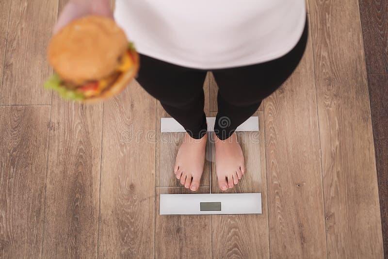 Conceito da dieta e do fast food Mulher excesso de peso que está na escala de peso que guarda o Hamburger do hamburguer Comida li imagens de stock