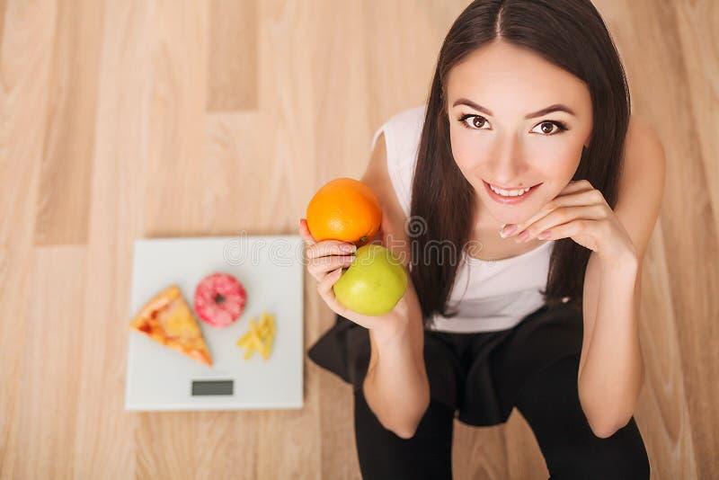 Conceito da dieta e do fast food Mulher excesso de peso que está na escala de peso que guarda a pizza Comida lixo insalubre Dieta imagem de stock royalty free