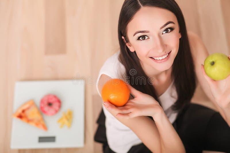 Conceito da dieta e do fast food Mulher excesso de peso que está na escala de peso que guarda a pizza Comida lixo insalubre Dieta imagens de stock