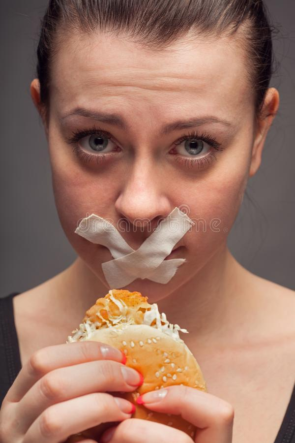 Conceito da dieta: mulher que mant?m um hamburguer com boca selado imagens de stock