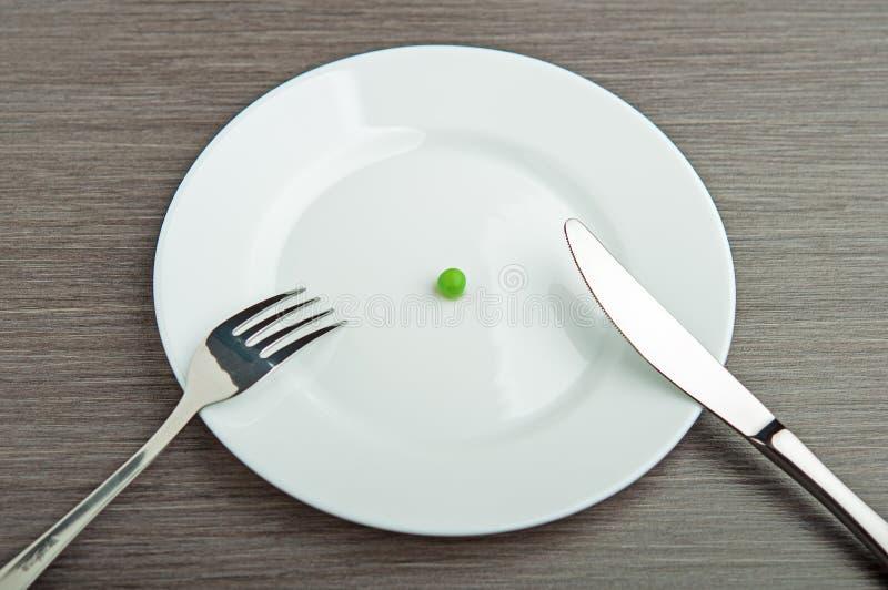 Conceito da dieta. uma ervilha em uma placa branca vazia fotografia de stock
