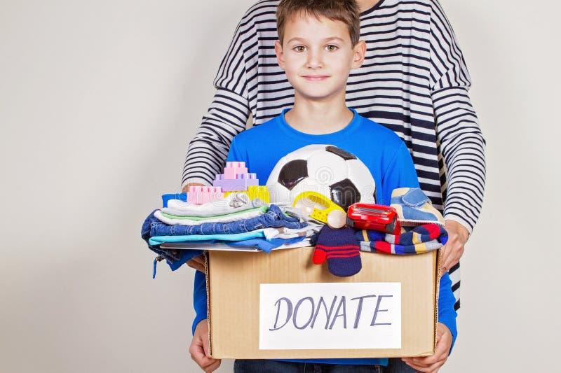 Conceito da doação Doe a caixa com roupa, livros e brinquedos na criança e na mão da mãe foto de stock