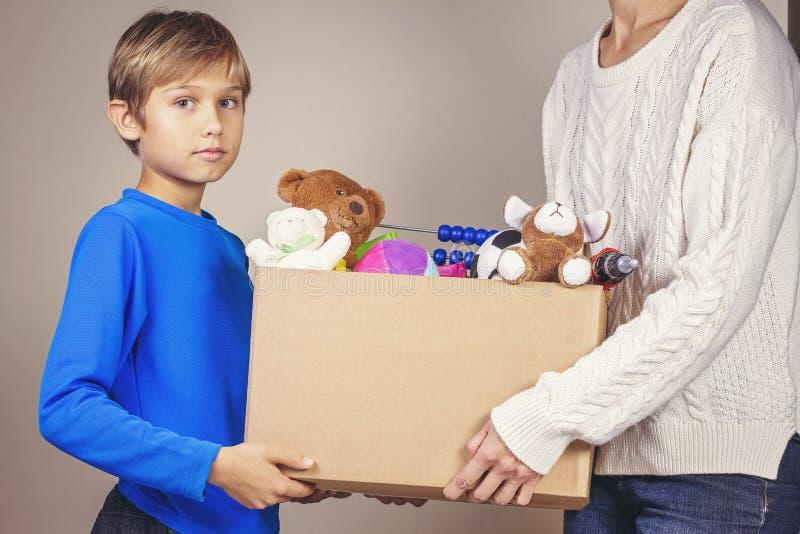 Conceito da doação Doe a caixa com roupa, livros e os brinquedos em membros da família entregam foto de stock