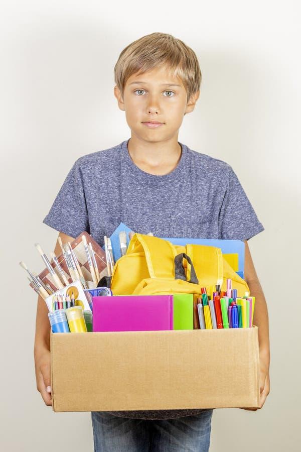 Conceito da doa??o Guardar da criança doa a caixa com livros, lápis e fontes de escola foto de stock royalty free