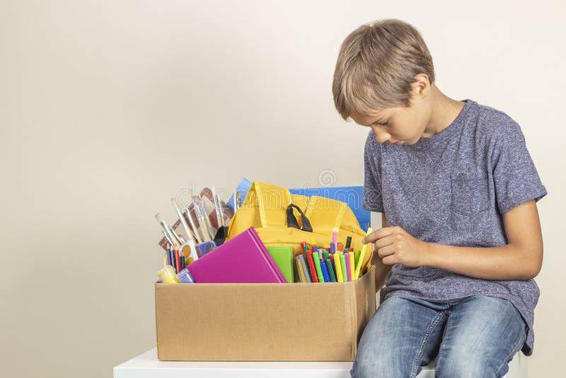 Conceito da doa??o Guardar da criança doa a caixa com livros, lápis e fontes de escola fotos de stock