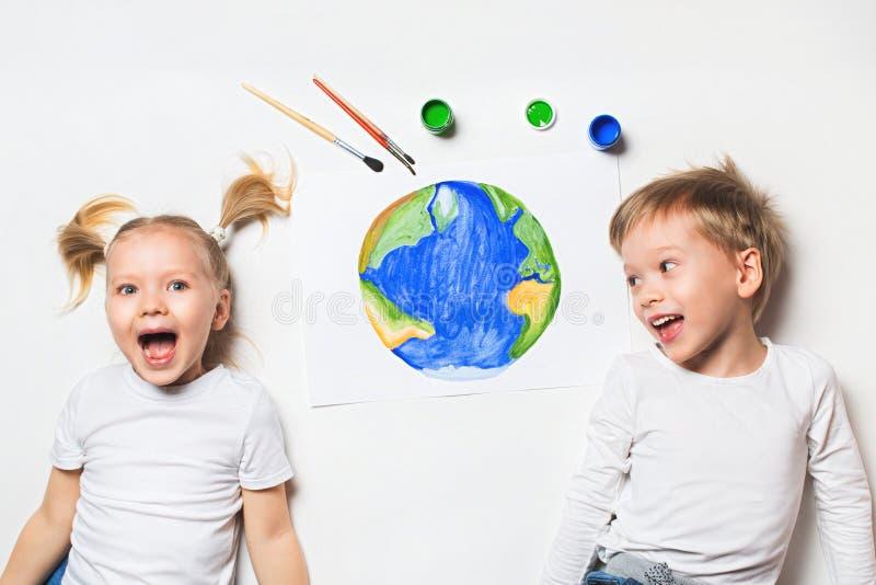 Conceito da ecologia com as duas crianças prety que pintam a terra no fundo branco fotografia de stock royalty free