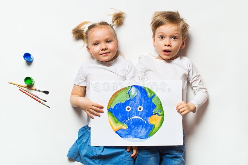 Conceito da ecologia com as duas crianças prety que pintam a terra triste no fundo branco fotografia de stock