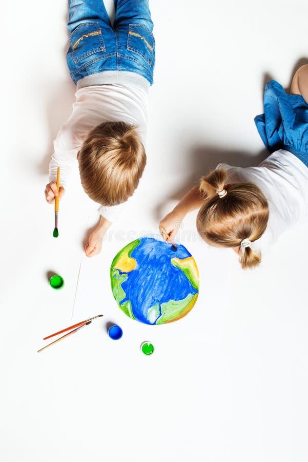 Conceito da ecologia com as duas crian?as prety que pintam a terra no fundo branco foto de stock royalty free