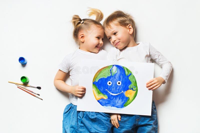Conceito da ecologia com as duas crian?as prety que pintam a terra no fundo branco fotos de stock royalty free