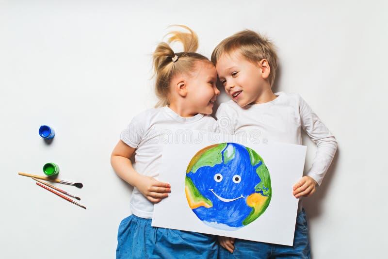 Conceito da ecologia com as duas crian?as prety que pintam a terra no fundo branco imagem de stock royalty free