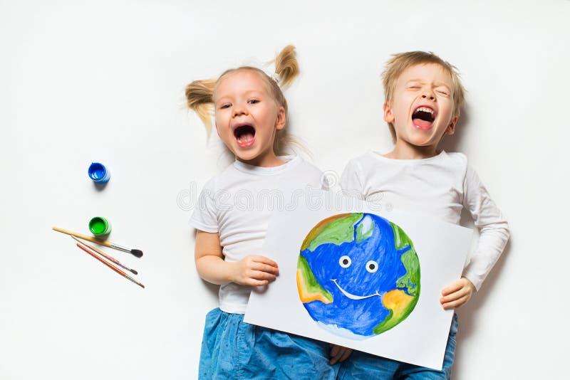 Conceito da ecologia com as duas crian?as prety que pintam a terra no fundo branco imagens de stock royalty free