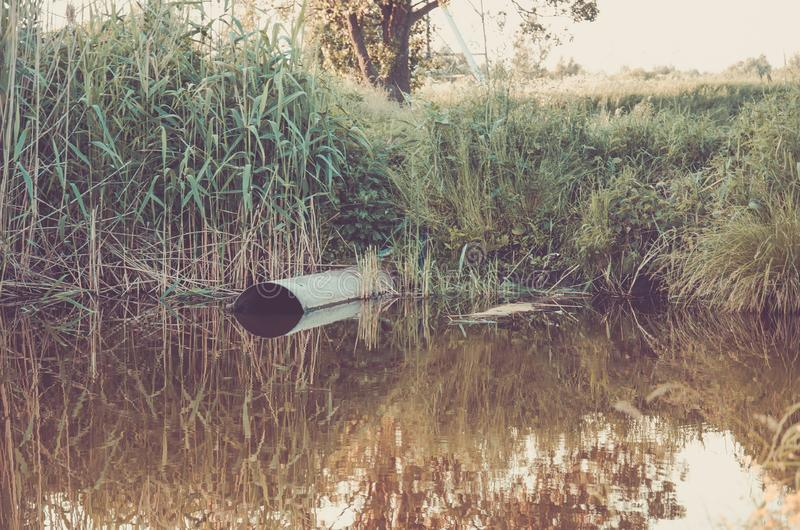 Conceito da ecologia: a tubulação de esgoto derrama para fora ao lago/água que jorra do esgoto ao lago fotografia de stock