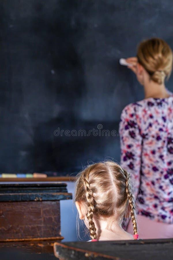Conceito da educação de escola primária pública com a moça que escuta o professor fêmea fotos de stock royalty free