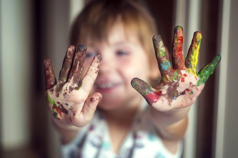Conceito da educação, da escola, da arte e do painitng - a exibição da menina pintou as mãos imagens de stock