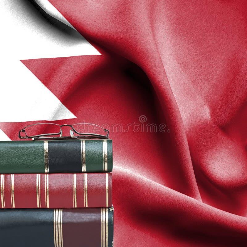 Conceito da educação - pilha de livros e de vidros de leitura contra a bandeira nacional de Barém imagem de stock royalty free