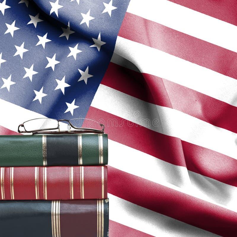 Conceito da educação - pilha de livros e de vidros de leitura contra a bandeira nacional do Estados Unidos da América imagem de stock royalty free