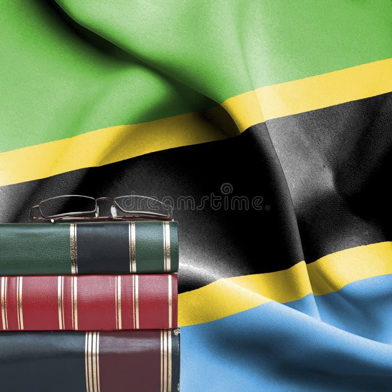 Conceito da educação - pilha de livros e de vidros de leitura contra a bandeira nacional de Tanzânia fotos de stock royalty free