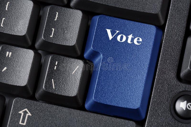 Conceito da eleição ou da democracia com o botão azul do voto no teclado preto Fim acima imagens de stock