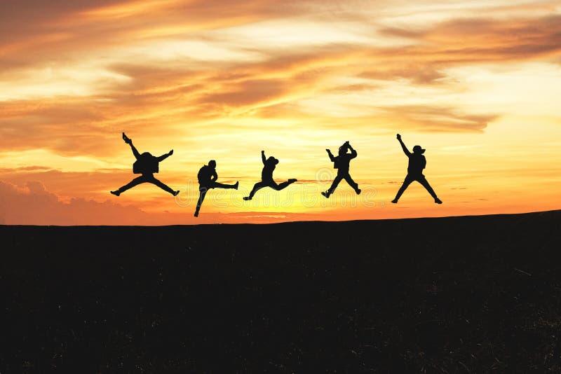Conceito da emoção Silhueta de um grupo de pessoas feliz que salta no por do sol na montanha imagens de stock